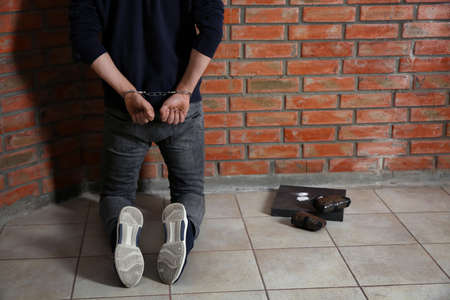 Male drug dealer in handcuffs near brick wall. Space for text 版權商用圖片