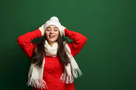 Young woman wearing warm clothes on color background, space for text. Winter season
