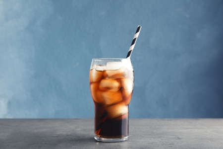 Glass of refreshing cola with ice on table against color background