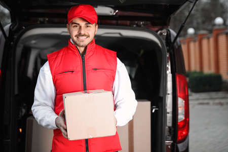 Deliveryman in uniform with parcel near van outdoors