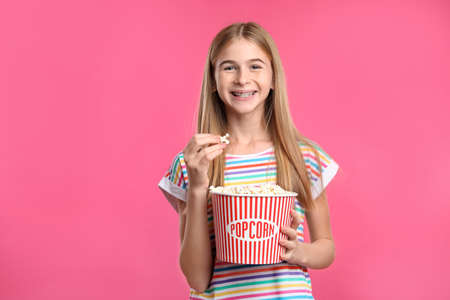 Teenage girl with popcorn during cinema show on color background