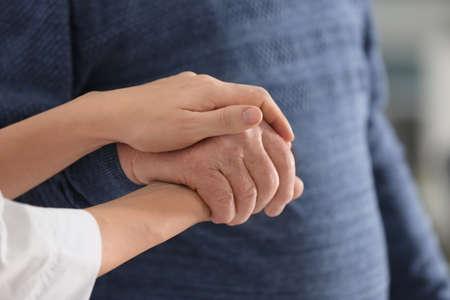Elderly man with female caregiver, closeup view