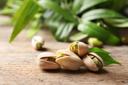 Organic pistachio nuts in shell on wooden table