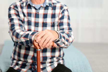 Elderly man with walking cane sitting on bed, closeup. Space for text