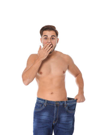 Fit man in oversized jeans on white background. Weight loss Stock Photo