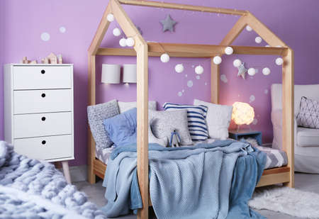 Child's room interior with comfortable bed and garland Archivio Fotografico