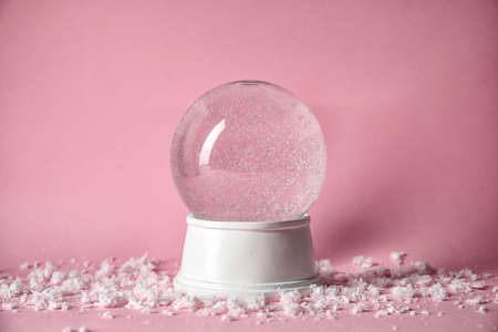 Magical empty snow globe on color background