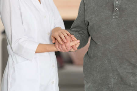 Elderly man with female caregiver on blurred background, closeup view