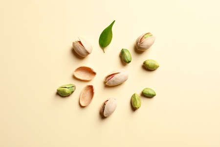 Composition with organic pistachio nuts on color background, flat lay 免版税图像