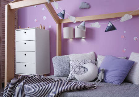 Comfortable bed in stylish child's room interior