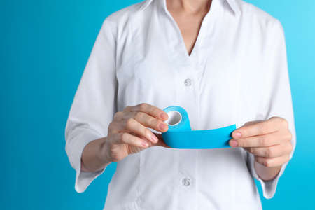 Female doctor holding elastic therapeutic tape on color background, closeup. Medical object