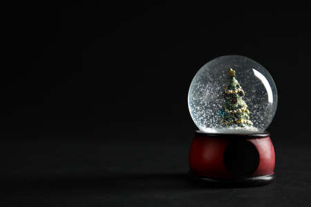 Snow globe with Christmas tree on dark background. Space for text 版權商用圖片