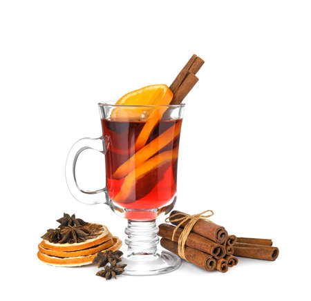 Composition with glass cup of mulled wine, cinnamon and dried orange slices on white background