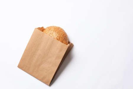 Bolsa de papel con bollo de sésamo sobre fondo blanco, vista superior. Espacio para texto Foto de archivo