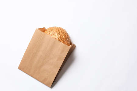 Paper bag with sesame bun on white background, top view. Space for text