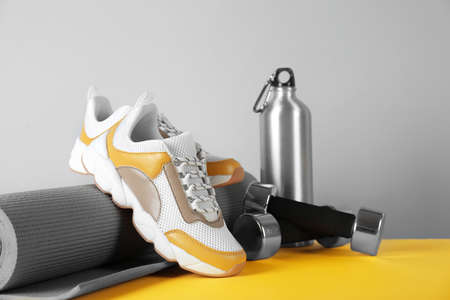 Composition of modern training shoes with mat, bottle and dumbbells on table Imagens