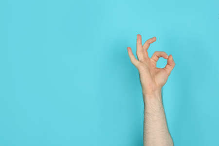 Young man showing OK gesture on color background. Space for text Stock Photo