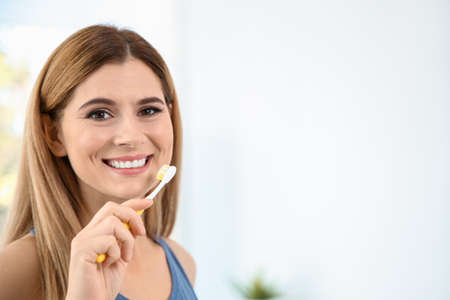 Portrait of woman with toothbrush on blurred background, space for text. Personal hygiene