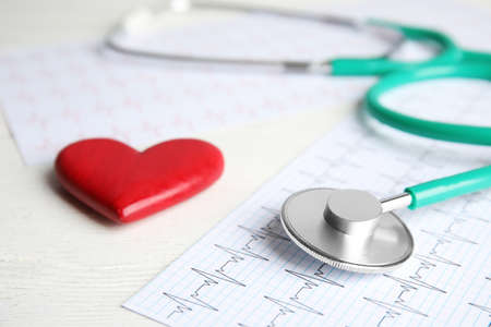 Stethoscope, red heart and cardiogram on wooden table. Cardiology concept Reklamní fotografie