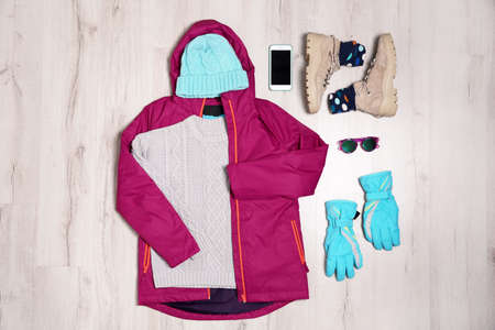 Flat lay composition with female clothes for winter vacation on wooden background
