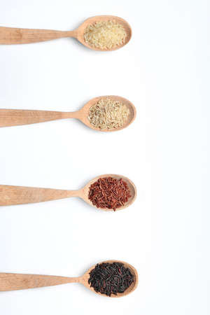 Spoons with different types of uncooked rice on white background, top view