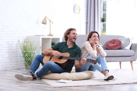 Young man playing acoustic guitar badly for displeased girlfriend in living room. Talentless musician Reklamní fotografie
