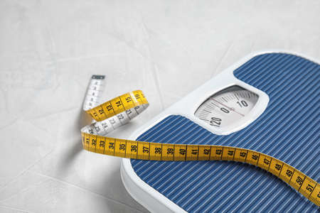 Scales and measuring tape on light background with space for text. Weight loss 写真素材 - 116225739