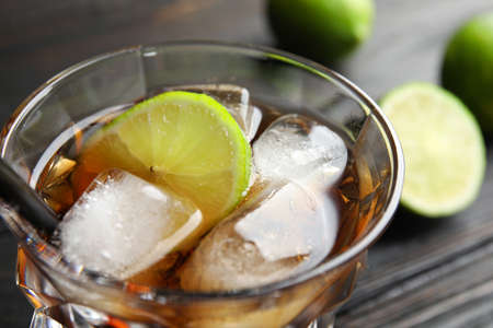 Glass of cocktail with cola, ice and cut lime on table, closeup