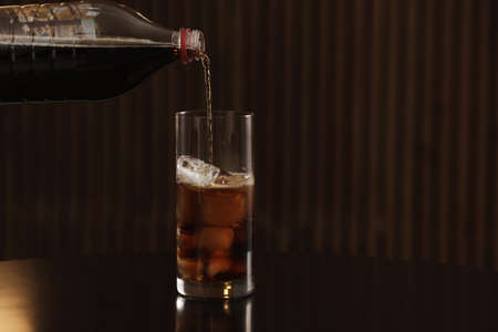 Pouring cola from bottle into glass with ice cubes on table against blurred background. Space for text