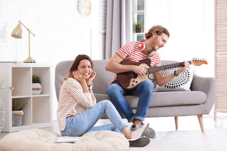 Young man playing electric guitar badly for displeased girlfriend in living room. Talentless musician Reklamní fotografie