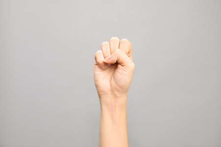 Woman showing S letter on grey background, closeup. Sign language