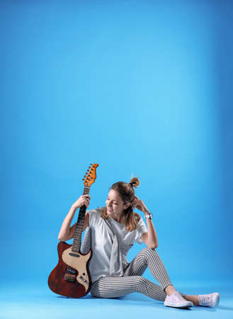Young woman with electric guitar on color background
