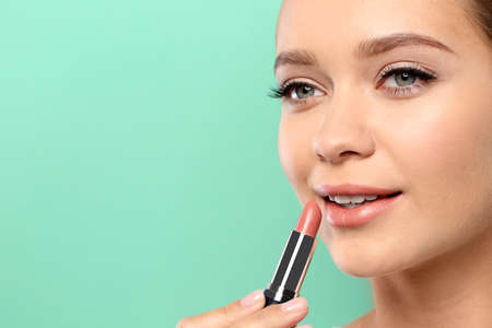 Beautiful woman applying nude lipstick on color background. Space for text