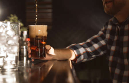 Man with glass of refreshing cola at bar counter, closeup. Pouring beverage