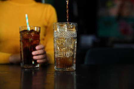 Pouring refreshing cola into glass and blurred woman on background Banque d'images