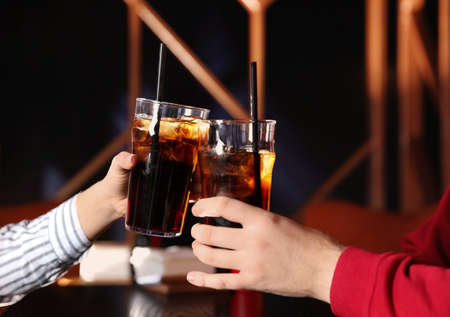 Young couple with glasses of refreshing cola at table indoors, closeup Фото со стока