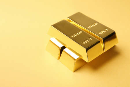 Precious shiny gold bars on color background. Space for text