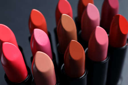 Set of different lipsticks on grey background, closeup. Cosmetic product