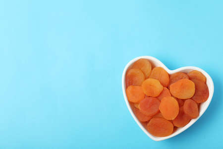 Bowl of dried apricots on color background, top view with space for text. Healthy fruit