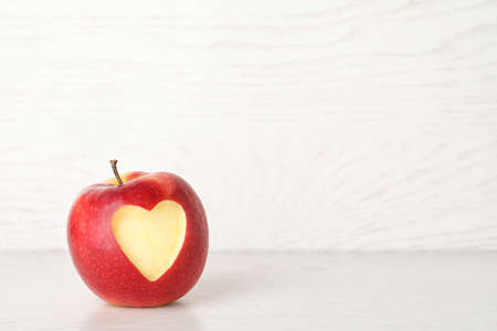 Red apple with carved heart on light background. Space for text Reklamní fotografie