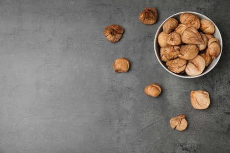 Bowl of dried figs on grey background, top view with space for text. Healthy fruit