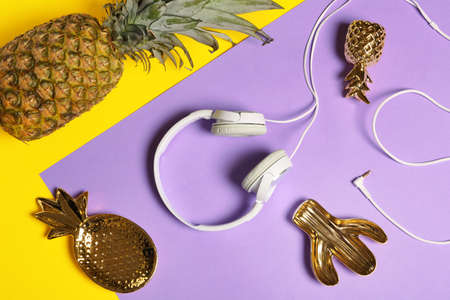 Flat lay composition with pineapple and headphones on color background