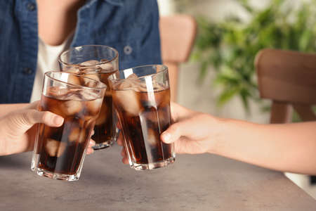 Friends with glasses of tasty refreshing cola at table, closeup view