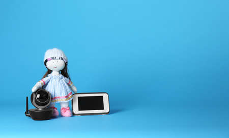 Modern CCTV security camera, doll and monitor on color background. Space for text
