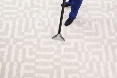 Man removing dirt from carpet with vacuum cleaner indoors, closeup. Space for text