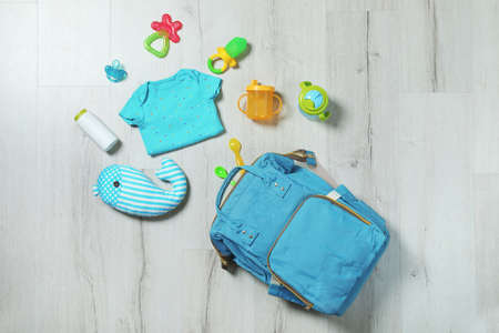 Flache Laienzusammensetzung mit Babyzubehör auf Holzuntergrund