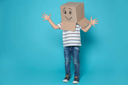 Cute little child wearing cardboard box with smiling face on color background Imagens