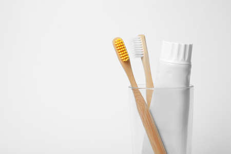 Glass with brushes and toothpaste on white background. Space for text