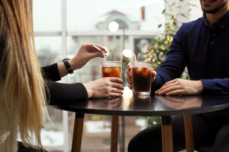 Couple with glasses of cold cola at table in cafe, closeup