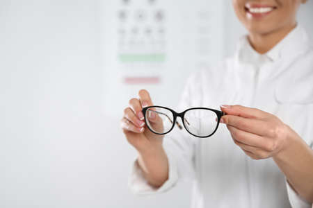 Female ophthalmologist with eyeglasses in clinic, closeup. Space for text